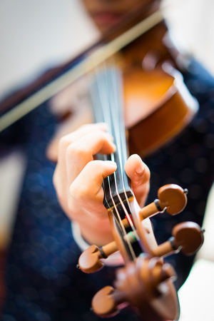 A young man is playing a violin in the sunday service at the church. Stock Photo