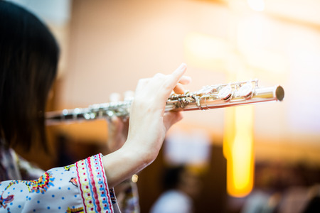 A woman is playing hymn song by her flute in the church.