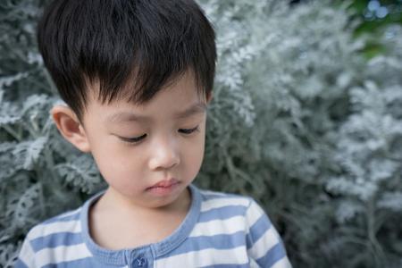 Een trieste jongen staat tussen het blad.