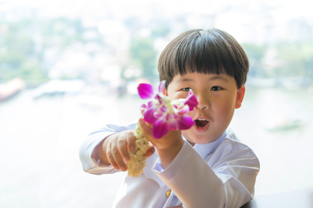 A boy wearing Thai dress, holding garland for give thanks his parents in Songkran day, Thai New Year day.
