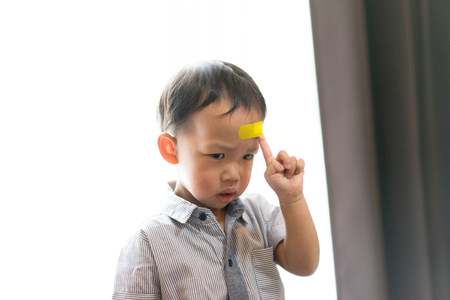 Children have ulcers at the head. His parents took the wound plaster. 스톡 콘텐츠