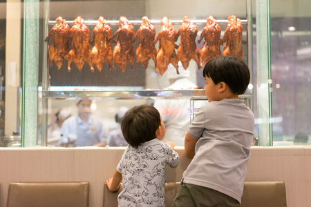 2 hungry brothers are watching a chef preparing roasted duck in Chinese restaurant 版權商用圖片