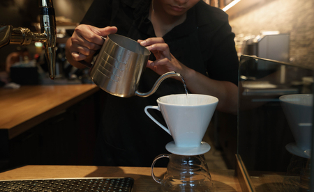 A barista wear black sweatshirt, She is spills hot water from teapot to coffee chrome drip on the wooden table in cafe shop.