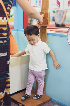 A boy is measuring height and weight to see his growth.