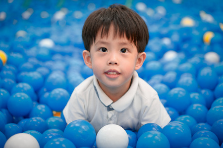 A happy boy is playing plastic balls at a playground.