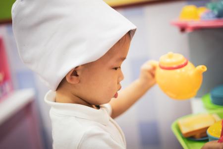 Ein kleiner Koch spielt auf dem Spielplatz ein Spielzeug für Essen und Teekannen.