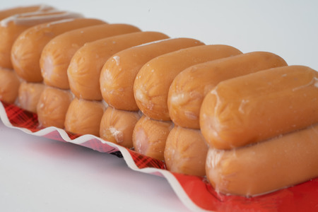 Sausages in plastic pack in white background.