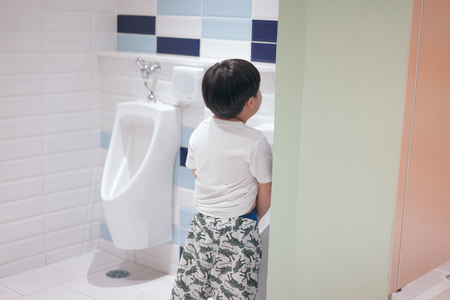 A boy is pissing himself in the bathroom.