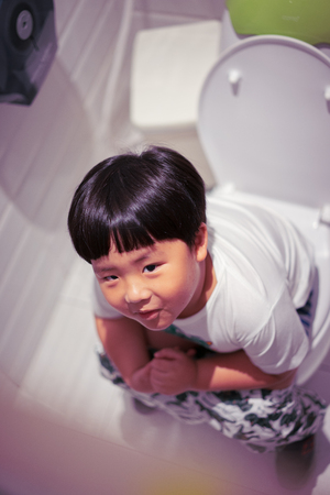 A boy is sitting on toilet with suffering from constipation or hemorrhoid. 스톡 콘텐츠