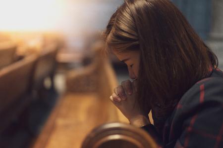 Una niña cristiana está sentada y orando con corazón humilde en la iglesia.