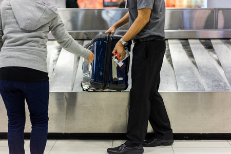 2 Aravelers take a luggage on the belt in airport after arrival to airport destination flight