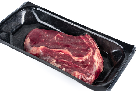 Raw steak in plastic pack in white background.