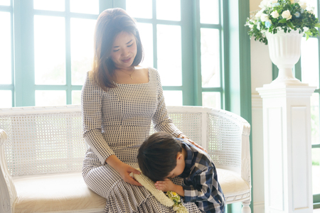 A lovely son give a Thai garland to his mom to show respect and give thank in a Mothers day.