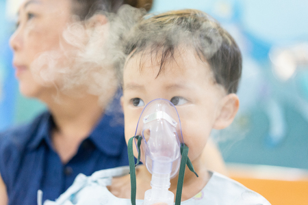 Großmutter kümmert sich um einen launischen Jungen, der nach einer Erkältung oder Grippe an einer Brustinfektion erkrankt ist und lange Zeit Schwierigkeiten beim Atmen und Husten hat. Daher ein Arzt, der Medizin mit einer Maske gibt.