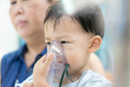Grandmother tack care a moody boy who is sick with a chest infection after a cold or flu has difficulty breathing and cough for a long time. Therefore, a doctor giving medicine with a mask.