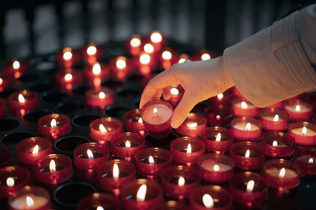 A woman is holding candle and praying near altar in church. Stock Photo