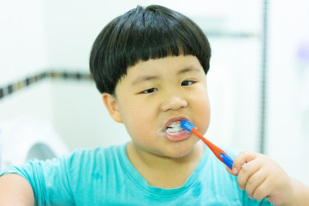 A boy try to brushes his teeth by himself in the restroom at night, before he go to bed. 版權商用圖片