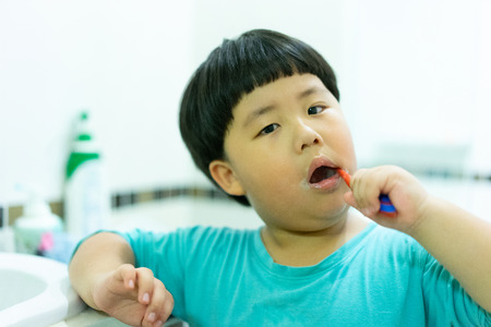 A boy try to brushes his teeth by himself in the restroom at night, before he go to bed. Foto de archivo