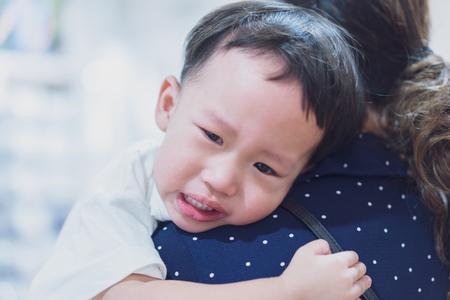 Un petit garçon asiatique étreint sa mère et pleure. Banque d'images