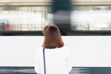A working women is wating a train in a trian station at Europe.