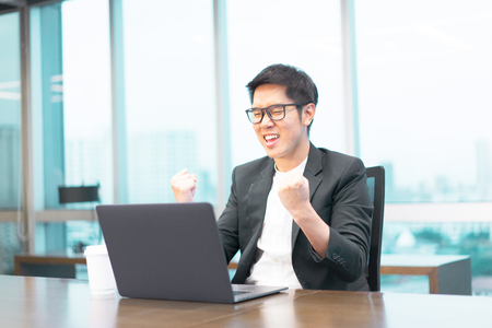 a happy businessman is working with his laptop computer and he have a cup of hot coffee on the table. Stock Photo