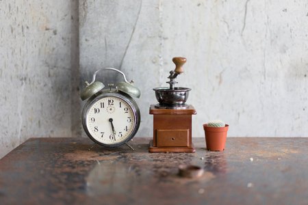 Old alarm clock and coffee grinder and cactus on the iron table rust in the concept of time and wake up to life.
