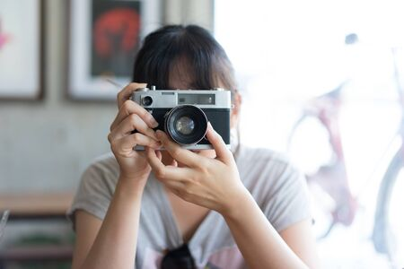 A hipster teenager is taking a film camera in the coffee cafe. Editorial