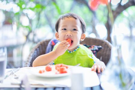 A boy is eating watermelon in the breakfast at the hotel.