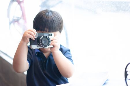 A boy is taking a Photo film camera in the coffee cafe. Editorial