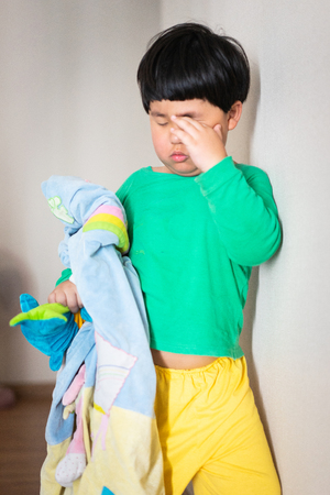 A sleepy child try to wake himself by standing and walking in the morning. Stock Photo