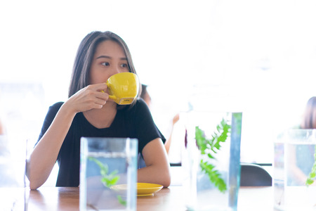 A hipster girl is drinking hot coffee in a loft cafe.