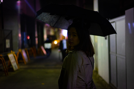 A woman is walking alone at the night street in the rainy season.