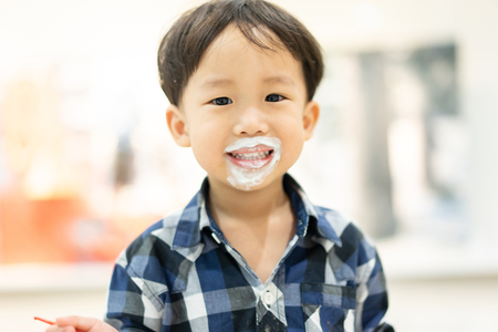 A happy boy is eating delicious ice-cream with sloppy mouth.