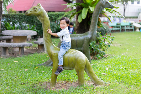A boy is playing and riding dinosaurs with his brother at the outdoor playground.