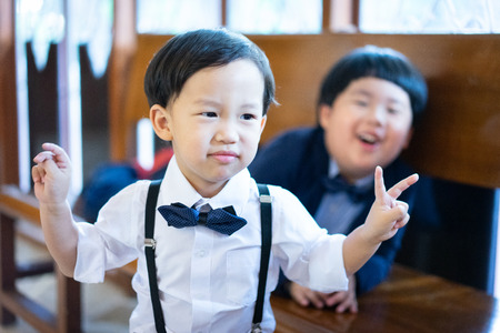 Naughty brothers make funny face, there are playing In the church with formal suit.