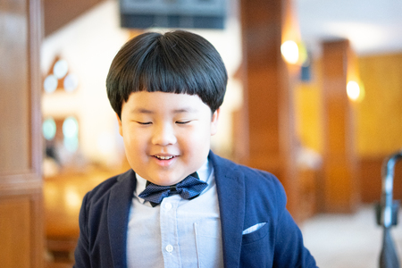 A naughty boy makes funny face, he is playing In the church with formal suit.