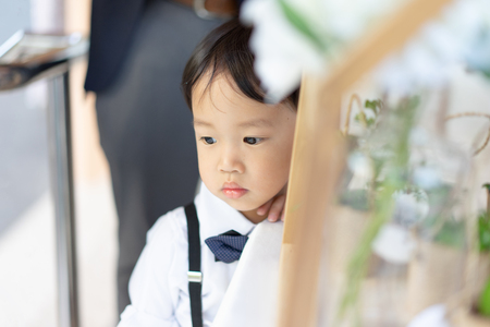 A shiny boy is waiting his father in the church with formal suit.