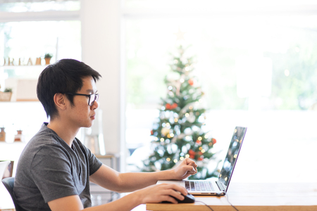 A freelance graphic designer is working hard in holiday with his computer.