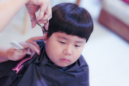 Grandmother is cutting hair of her chubby grandson at home.