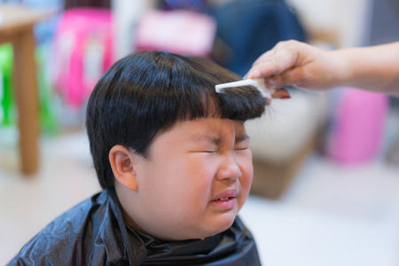 A chubby boy is hurted and crying while his grandmother is cutting his hair at home.