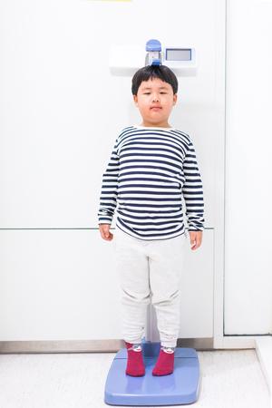 Un niño gordo mide su altura y su peso él mismo en el hospital.