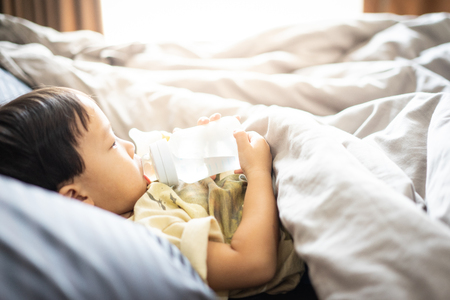 A boy is sucking a bottle of milk in the morning while watching TV in the bed in the bedroom.