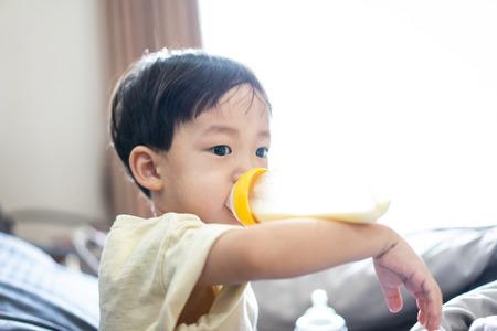 Un garçon suce une bouteille de lait le matin en regardant la télévision dans le lit de la chambre. Banque d'images