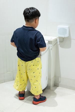 Een jongen plast zichzelf in de badkamer. Stockfoto