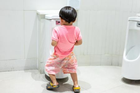 Een jongen plast zichzelf in de badkamer.
