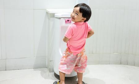 Un chico se orina en el baño. Foto de archivo