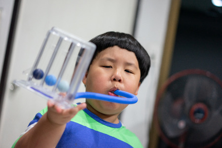 A fat boy is testing and administering lungs with a tri-ball dryer. Stok Fotoğraf