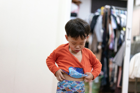 A boy tried to wear pajamas by himself before he go to bed at night.