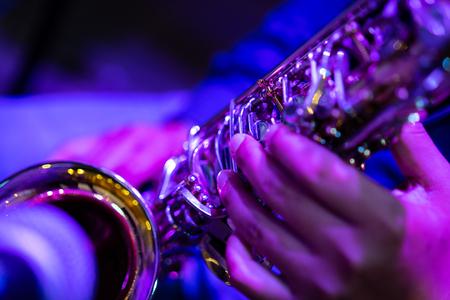 한 예술가의 클로즈업 사진이 결혼식에서 색소폰을 연주하고 있습니다.