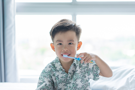 A cute boy is brushing his teeth in the morning on the bed.
